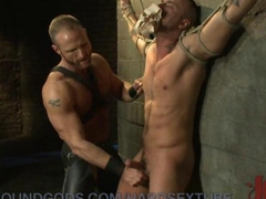 This sexy muscle daddy has his slave boy bound and helpless while he sexually torments him. He grabs him by the balls and aggressively handles his cock before fucking the cum out of him.
