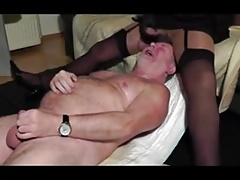 A man wearing women's clothes masturbating with another man